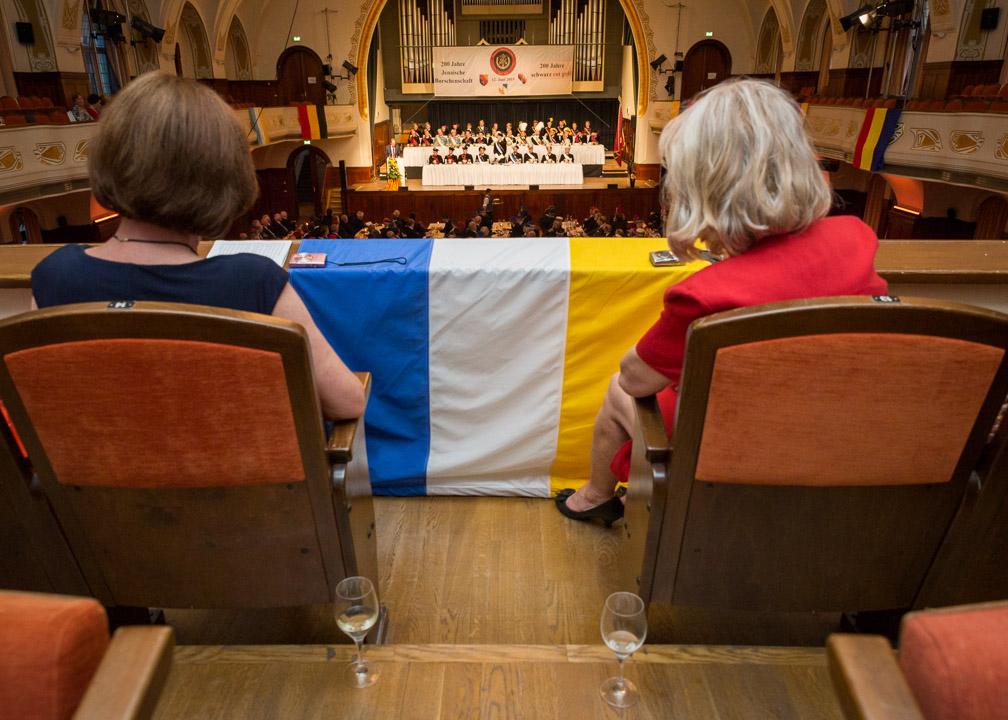 Damen dürfen den Festkommers vom Balkon des Festsaals aus betrachten. Die Flaggen, welche von den Balkonen hängen, zeigen die Farben der Jenaischen Burschenschaften und Ihrer Freundschafts- und Kartellbünde. Im Vordergrund ist beispielsweise die Flagge von Teutonia Jena zu sehen.