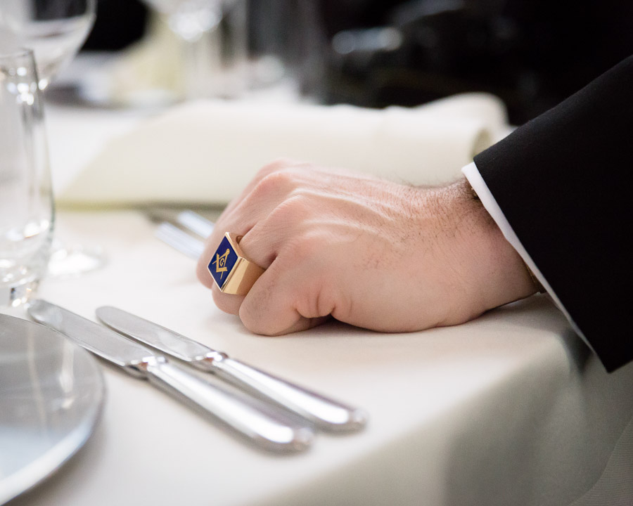 Hand of a Freemason during New Year's Celebration, Bonn, Germany, 2014. The ring shows the square and compasses, both Masonic symbols.